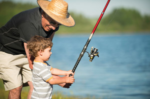 Cute little boy fishing with his grandfather