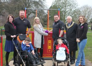 Stephanie cutting the ribbon with the chairman and other fundraisers and two boys in wheelchairs