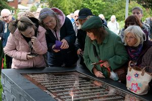 People look at names on plaque